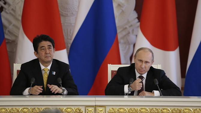 Russian President Vladimir Putin, right, speaks at a final news conference alongside visiting Japanese Prime Minister Shinzo Abe in Moscow's Kremlin, Monday, April 29, 2013. Abe is in Russia on an official visit. (AP Photo/Ivan Sekretarev, pool)