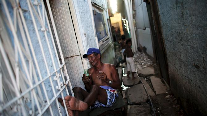 A man sits at the entrance of his house in a slum of Recife