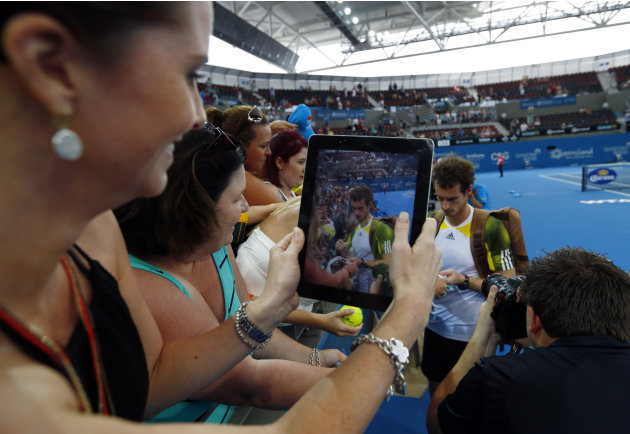A tennis fan takes a picture on her tablet device as Murray of Britain signs autographs after defeating Dimitrov of Bulgaria in the men's final match at the Brisbane International tennis tournament