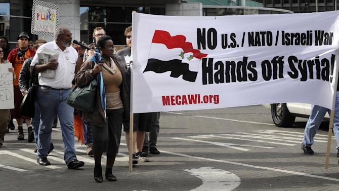 A couple hundred protestors peacefully demonstrate against the impending attack on Syria in Detroit, Michigan on Sunday Sept. 8, 2013. Members of the Michigan Committee for Emergency War and Injustice were among the marchers. (AP Photo/The Detroit News, Charles V. Tines)