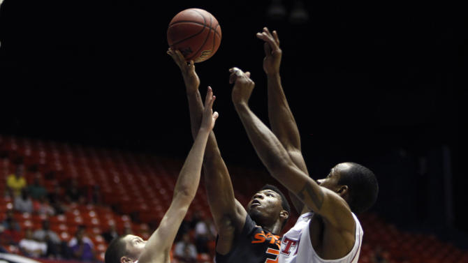 Oklahoma State's Marcus Smart, center, goes up for the basket against NC State's players Scott Wood, left, and Lorenzo Brown during a NCAA college basketball game in Bayamon, Puerto Rico, Sunday, Nov. 18, 2012. (AP Photo/Ricardo Arduengo)