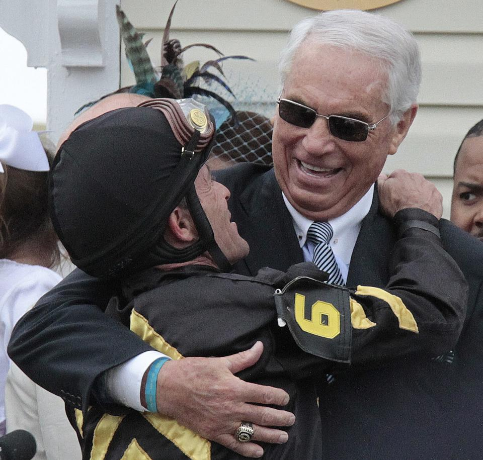 Jockey Gary Stevens, left, embraces trainer D. Wayne Lukas in the winner's circle after Oxbow won the 138th Preakness Stakes horse race at Pimlico Race Course, Saturday, May 18, 2013, in Baltimore. (AP Photo/Garry Jones)
