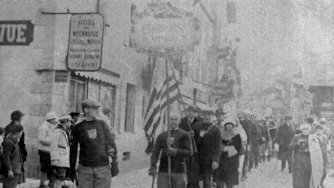 FILE - In this Jan. 25, 1924, file photo, a man carries the American flag, as the United States is represented during opening ceremonies for the I Winter Olympics in Chamonix, France. The teams of all the nations represented, bearing their national flags and emblems, paraded from the City Hall to the skating rink, where the actual competitions began the following day. (AP Photo/File)