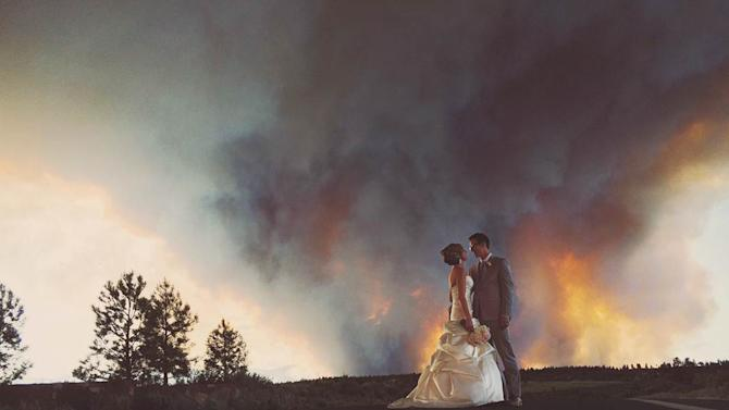 In this Saturday, June 7, 2014 photo provided by Josh Newton, newlyweds Michael Wolber and April Hartley pose for a picture near Bend, Ore., as a wildfire burns in the background. Because of the approaching fire, the minister conducted an abbreviated ceremony and the wedding party was evacuated to a downtown Bend park for the reception. (AP Photo/Josh Newton)