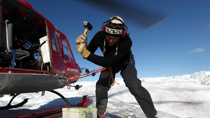 In this July 19, 2011 photo, attached by rope to a waiting helicopter, Arctic researcher Carl Gladish of New York University hammers a steel stake into ice, securing a newly-deployed GPS seismometer, or Geopebble, designed to track glacial movement near the edge of the Greenland ice sheet, atop Jakobshavn Glacier, outside Ilulissat, Greenland. The chief researcher, NYU's David Holland, hopes to eventually deploy scores of the devices to help measure ice loss in Greenland. (AP Photo/Brennan Linsley)