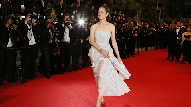 Actress Marion Cotillard poses for photographers as she arrives for the screening of In the Name of my Daughter (L'homme qu'on aimait trop) at the 67th international film festival, Cannes, southern France, Wednesday, May 21, 2014. (AP Photo/Alastair Grant)