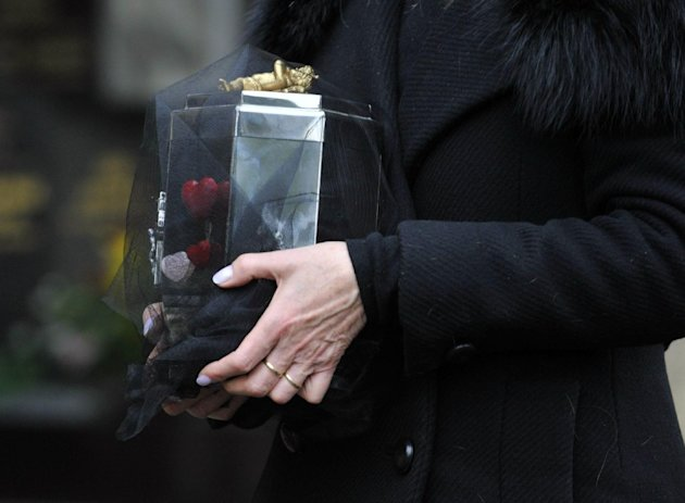 Dagmar Havlova, the widow of Czech President Vaclav Havel, hold the urn with the Havel´s ashes prior to burying it to the family tomb at the Vinohrady Cemetery in Prague Wednesday, Jan. 4, 2012. Vaclav Havel died Dec. 18 at age 75. (AP Photo/CTK, Roman Vondrous) SLOVAKIA OUT