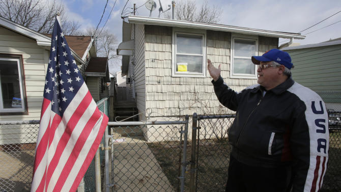 Anthony Gambino points to the house he rents, Wednesday, Jan. 23, 2013 in the borough of Staten Island in New York. The house was badly damaged by Superstorm Sandy and renovations are not yet complete. Meanwhile, because of the extreme cold weather, Gambino has been spending the night in a tent nearby operated by the volunteer group Cedar Grove Community Hub.  (AP Photo/Mark Lennihan)