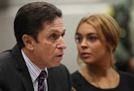 Actress Lindsay Lohan appears in Los Angeles court with her new attorney Mark Heller, left, for a pretrial hearing, Wednesday, Jan. 30, 2013, in a case filed over the actress' June car crash. Lohan faces three misdemeanor charges and a return to jail if convicted in the case or if a judge finds she violated her probation. (AP Photo/David McNew, Pool)