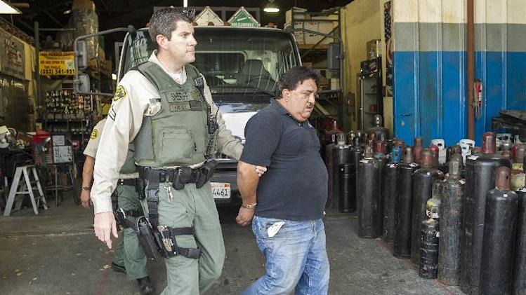 "Los Angeles County Sheriff's deputy Jim Phillips, left, detains Federico Valencia after a search warrant at Victor Welding Supply, Co. in Los Angeles Friday, March 22, 2013. A joint operation dubbed ""No Laughing Matter"" by the Food and Drug Administration's Office of Criminal Investigations and Los Angeles Sheriffs say the use of nitrous oxide as a recreational drug has grown from a rave phenomenon to mainstream use in recent years propelled by the ease of social media to advertise illegal parties, especially among teenagers. (AP Photo/Damian Dovarganes)"