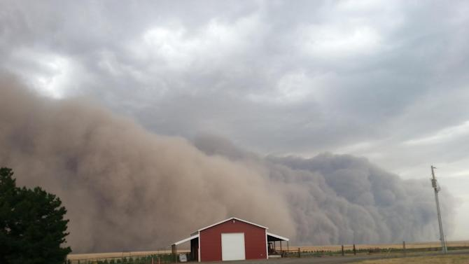 A massive, dramatic dust storm moves toward a barn near Harrington Wash., Tuesday Aug. 12, 2014. More often associated with the Southwest the dust storm blew through Eastern Washington and north Idaho on Tuesday evening in advance of thunderstorms, lightning and rain. (AP Photo/Lacey Hirst)