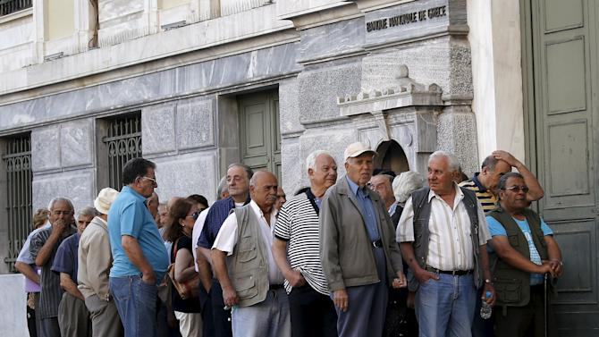 Pensioners wait outside a bank in Athens