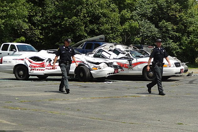 Sheriff officers walk past crushed cruisers at the Orleans County Sheriff&#39;s Department in Newport, Vt., Thursday, Aug. 2, 2012. Authorities say 34-year old Vermont farmer Roger Pion, angry over a recent arrest last month on charges of resisting arrest and marijuana possession, used a large tractor like a monster truck, destroying seven police cruisers. (AP Photo/Northland Journal, Scott Wheeler)