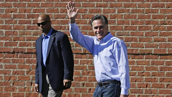 Republican presidential candidate and former Massachusetts Gov. Mitt Romney is accompanied by a U.S. Secret Service agent as he leaves debate preparation at a hotel in Columbus, Ohio, Saturday, Oct. 13, 2012. (AP Photo/Charles Dharapak)