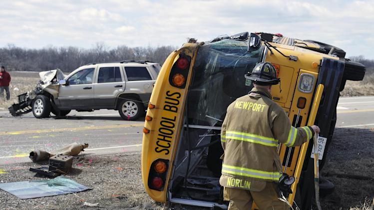 Investigators gather evidence from the scene of a three vehicle accident, including a school bus where the driver of a Jeep Wrangler was killed on Friday, April 5, 2013, near Wadsworth, Ill.  Over two dozen school children were on the bus, most receiving minor injuries. (AP Photo/Jim Prisching)