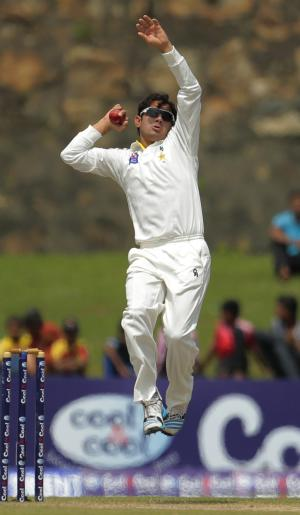 Pakistani cricketer Saeed Ajmal bowls during the fourth day of the first test cricket match between Sri Lanka and Pakistan in Galle, Sri Lanka, Saturday, Aug. 9, 2014. (AP Photo/Eranga Jayawardena)