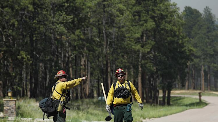 Black Forest Fire Dept. officers examine an evacuated neighborhood, prepping the area for encroachment of the wildfire in the Black Forest area north of Colorado Springs, Colo., on Wednesday, June 12, 2013. The number of houses destroyed by the Black Forest fire could grow to around 100, and authorities fear it's possible that some people who stayed behind might have died. (AP Photo/Brennan Linsley)