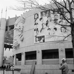 """This April 1964 photo provided by The Andy Warhol Foundation for the Visual Arts, Inc. shows a 20x20 foot mural depicting mug shots of the NYPD's 13 most-wanted criminals by Andy Warhol, mounted on the curved facade of the New York State Pavilion at the 1964 New York World's Fair in the Queens borough of New York. The fair celebrated """"The World of Tomorrow,"""" but Warhol may have been ahead of his time. His monumental piece commissioned specifically for the fair was deemed too edgy for the family-friendly event and painted over just before opening day. Now, 50 years later, the work is the focus of a museum exhibition being staged on the very fairgrounds where the pop-art provocateur was infamously censored. (AP Photo/The Andy Warhol Foundation for the Visual Arts, Inc./Artists Rights Society)"""