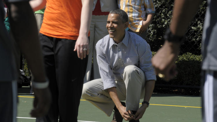 President Barack Obama ties his shoe while playing basketball during the annual Easter Egg Roll on the South Lawn of the White House in Washington, Monday, April 1, 2013. (AP Photo/Susan Walsh)