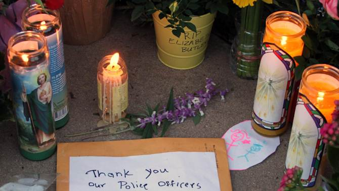 "A note is left at a memorial site for detectives Elizabeth Butler and Loran ""Butch"" Baker at Santa Cruz Police Headquarters in Santa Cruz, Calif., Wednesday, Feb. 27, 2013. The detectives, responding to a sexual assault report Tuesday afternoon, were killed at the doorstep of a suspect who was chased down and killed half an hour later. (AP Photo/Thomas Mendoza)"