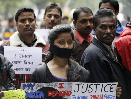 Protesters hold banners and wear black ribbons during a rally in New Delhi on December 30, 2012, following the cremation of a murdered gang-rape victim in the Indian capital. Her family will not rest until her killers are hanged, her brother said on Monday.