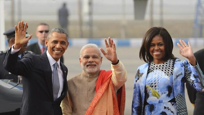 Indian Prime Minister Narendra Modi, center, U.S. President Barack Obama and first lady Michelle Obama wave to the gathering at the Palam Air Force Station in New Delhi, India, Sunday, Jan. 25, 2015. Obama's arrival Sunday morning in the bustling capital of New Delhi marked the first time an American leader has visited India twice during his presidency. Obama is also the first to be invited to attend India's Republic Day festivities, which commence Monday and mark the anniversary of the enactment of the country's democratic constitution. (AP Photo)