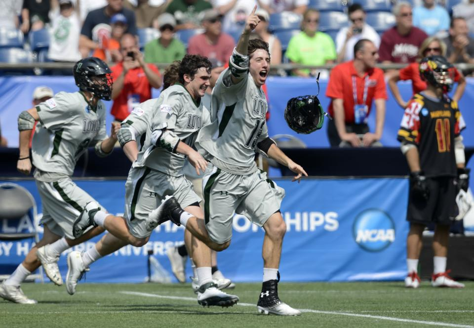 Loyola lacrosse players, including Greg Catalano, center, rush the field after defeating Maryland 9-3 in the Division I NCAA men's lacrosse championship game at Gillette Stadium in Foxborough, Mass., Monday, May 28, 2012. (AP Photo/Gretchen Ertl)
