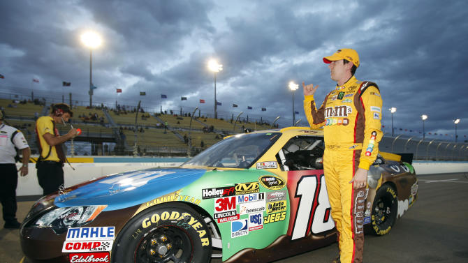 Kyle Busch gestures to cheering fans after winning the pole during qualifying for Sunday's NASCAR Sprint Cup Series auto race, Friday, Nov. 9, 2012, at Phoenix International Raceway in Avondale, Ariz. (AP Photo/Paul Connors)
