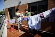 Women hang laundry on a balcony in a building they have occupied in Seville. Spain posted a 24.4% unemployment rate in the first three months of the year as the economy slipped into recession with activity shrinking for the second straight quarter