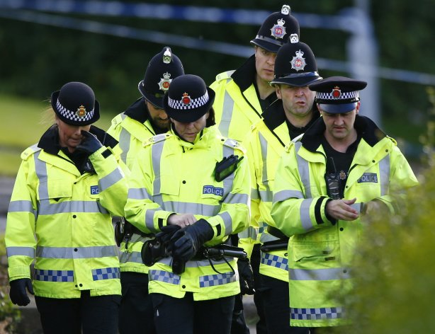 Police officers gather at the scene where two female police officers were killed in Hattersley near Manchester, northern England September 18, 2012. Two unarmed policewomen were killed in a shooting in Manchester on Tuesday in an attack likely to reignite a long-running debate in Britain over whether officers should carry guns.