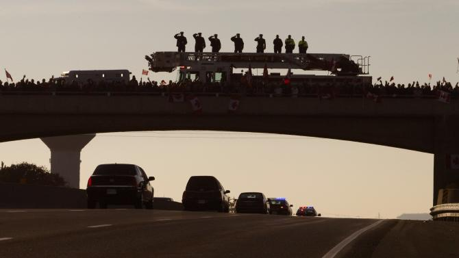 """Firemen salute from the top of their truck to honour Corporal Cirillo as the motorcade and hearse carrying his body passes along nation's """"Highway of Heroes"""", enroute to Hamilton, Ontario"""