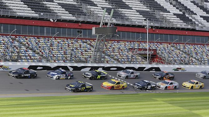 A pack of cars drives past the start/finish line moments before a wreck on the backstretch during NASCAR auto race testing at Daytona International Speedway, Friday, Jan. 11, 2013, in Daytona Beach, Fla. (AP Photo/John Raoux)