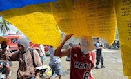 <p>Residents look at the lists of missing people displayed in New Bataan, Compostela province, on December 12, 2012. The death toll from the strongest typhoon to hit the Philippines this year has topped 1,000 and could still rise sharply, the government said on Sunday.</p>
