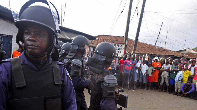 Liberia security forces dressed in riot gear, left, control a crowd of people in the West Point area, as the government clamps down on the movement of people to prevent the spread of the Ebola virus in Monrovia, Liberia, Wednesday, Aug. 20, 2014. Security forces deployed Wednesday to enforce a quarantine around a slum in the Liberian capital, stepping up the government's fight to stop the spread of Ebola and unnerving residents. (AP Photo/Abbas Dulleh)