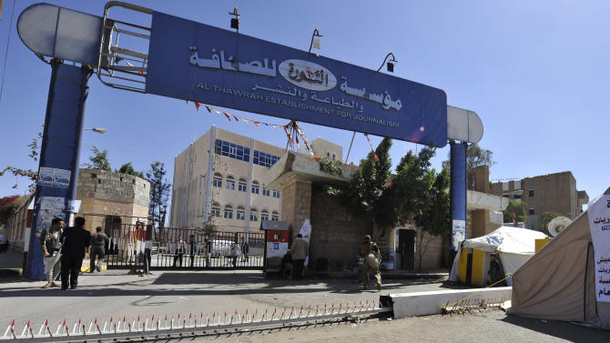 Yemenis walk through the gate of newspaper al-Thawra, a day after Houthi rebels stormed the building in Sanaa, Yemen, Wednesday. Dec. 17, 2014. Yemen's powerful Shiite rebels shut down a strategic Red Sea port on Wednesday, and stormed the offices of the country's main state newspaper, officials said. (AP Photo/Hani Mohammed)
