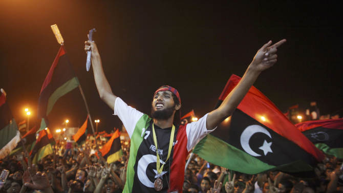 People celebrate the capture in Tripoli of Moammar Gadhafi's son and one-time heir apparent, Seif al-Islam, at the rebel-held town of Benghazi, Libya, early Monday, Aug. 22, 2011. Libyan rebels raced into Tripoli in a lightning advance Sunday that met little resistance as Moammar Gadhafi's defenders melted away and his 40-year rule appeared to rapidly crumble. The euphoric fighters celebrated with residents of the capital in the city's main square, the symbolic heart of the regime. (AP Photo/Alexandre Meneghini)