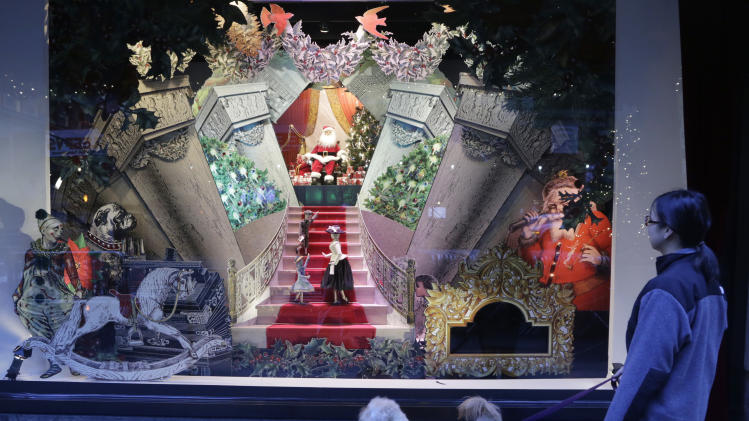 This Nov. 18, 2013 photo shows a woman walking her dog past a vintage Santa Claus holiday window display at Lord & Taylor department store in New York. Forget window shopping, some of Manhattan's biggest and most storied retailers say their elaborate seasonal window displays are a gift to passers-by. (AP Photo/Mark Lennihan)