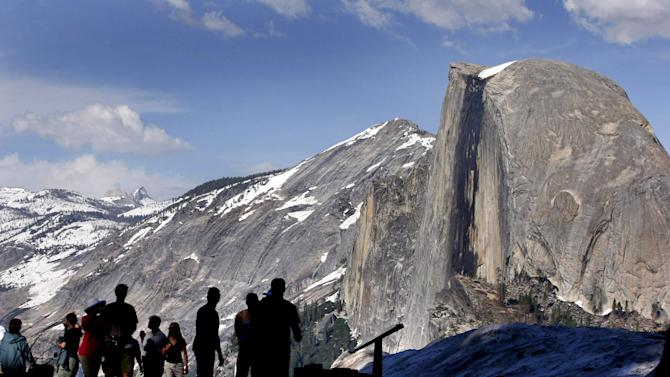 FILE - In this 2005 file photo, visitors view Half Dome from Glacier Point at Yosemite National Park, Calif. Visitors to America's national parks will encounter fewer rangers, find locked restrooms and visitors centers, and see trashcans emptied less often if 5 percent across-the-board cuts are enacted by sequestration. A National Park Service internal memo obtained by The Associated Press compiles a list of cuts in services in parks from Cape Cod to Yosemite. It's the result of an order by Park Service Director John Jarvis in January that asked superintendents to show how they will absorb the funding cuts. (AP Photo/Dino Vournas, File)