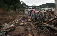 Rescue workers carry the recovered body of a landslide victim in Nova Friburgo, Rio de Janeiro state, Brazil, Saturday, Jan. 15, 2011. After four nights of torrential rains, mudslides have killed more than 500 people in the Rio de Janeiro area.
