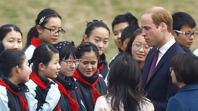 Britain's Prince William chats with students during a visit to a Premier League training camp at a school in Shanghai