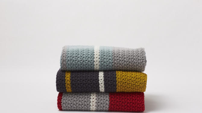 This photo provided by AllModern.com shows Coyuchi's chunky, yarn dyed knit throws that bring cozy and contemporary together. Cozying up in a favorite sweater is one of the distinct pleasures of autumn. This fall, designers and retailers are stitching up sweater motifs on an array of home decor, too. (AP Photo/AllModern.com)