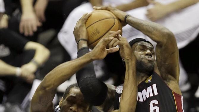 San Antonio Spurs' Kawhi Leonard (2) and Miami Heat's LeBron James (6) battle for a rebound during the first half at Game 4 of the NBA Finals basketball series, Thursday, June 13, 2013, in San Antonio. (AP Photo/David J. Phillip)