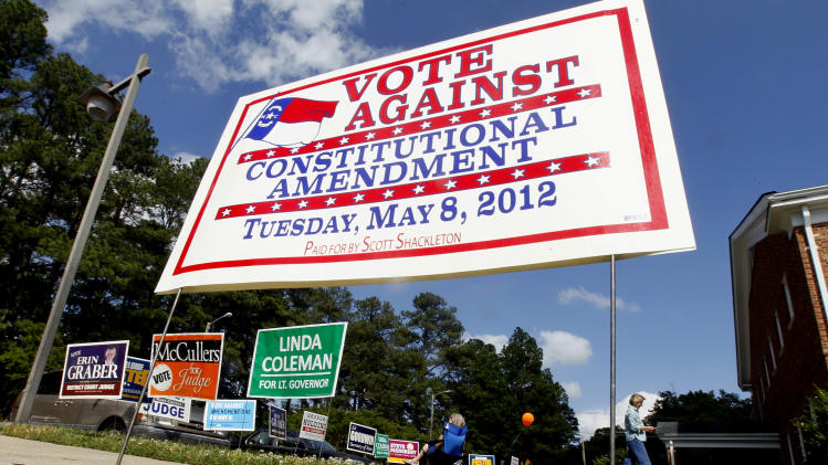 Constitutional Amendment signs are seen with others at the entrance to a polling location at Hudson Memorial Presbyterian Church in Raleigh, N.C., Tuesday, May 8, 2012. While a constitutional amendment that would ban gay marriage is driving turnout in North Carolina' primary elections on Tuesday, North Carolina voters are also choosing nominees for governor, 13 congressional districts, nine of the 10 Council of State positions and dozens of General Assembly seats. (AP Photo/Gerry Broome)