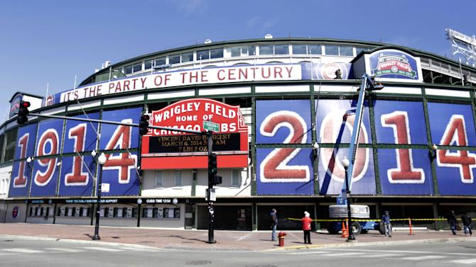 In this March 24, 2014, file photo, Wrigley Field in Chicago sports large numerals celebrating the iconic park's 100th anniversary. Cubs owner Tom Ricketts thinks a move to the suburbs might be lucrative but says his team remains committed to refurbishing century-old Wrigley Field. The Cubs won approval from Chicago's City Council last July for a $500 million renovation that would include installation of a 5,700-square-foot video scoreboard at Wrigley, which turns 100 on April 23