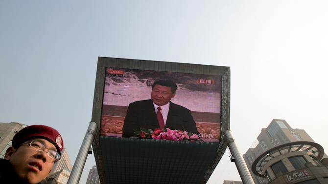 A security guard stands near a huge screen showing a live broadcast of China's new Communist Party General Secretary Xi Jinping speaking during a press event to introduce the newly-elected members of the Politburo Standing Committee in Beijing Thursday Nov. 15, 2012. The seven-member Standing Committee, the inner circle of Chinese political power, was paraded in front of assembled media on the first day following the end of the 18th Communist Party Congress. (AP Photo/Andy Wong)