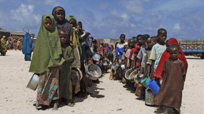 FILE - In this Monday, Aug. 15, 2011 file photo, children from southern Somalia hold their pots as they line up to receive cooked food in Mogadishu, Somalia. Officials in East Africa say a report to be released this week by two U.S. government-funded famine and food agencies gives the highest death toll yet from Somalia's 2011 famine, estimating that 260,000 people died - more than double previous estimates. (AP Photo/Farah Abdi Warsameh, File)