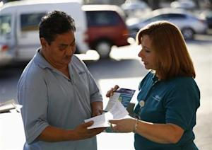 Acosta, patient care coordinator at AltaMed, speaks to a man during a community outreach on Obamacare in Los Angeles