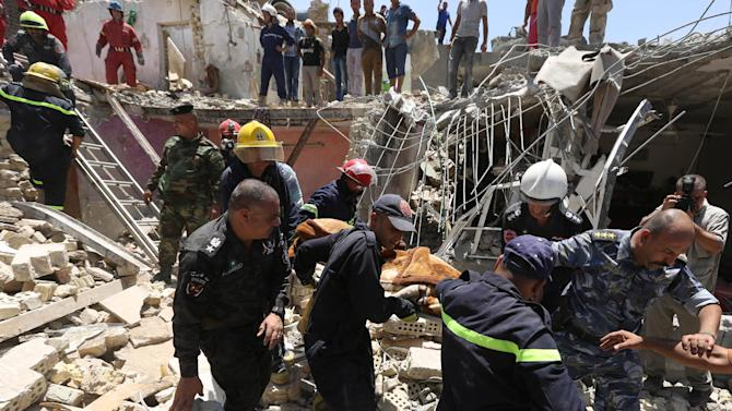 Rescuers evacuate the body of a victim killed from a bombing in the eastern neighborhood of New Baghdad. Iraq, Monday, July 6, 2015. At least a dozen civilians were killed on Monday when a Russian-made fighter jet accidentally dropped a bomb over a Baghdad neighborhood, officials said. (AP Photo/ Hadi Mizban)
