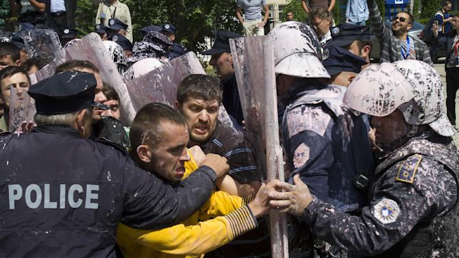 Kosovo police splashed with paint clash with hardline opposition members protesting a deal with Serbia in capital Pristina, Kosovo, Thursday, June 27, 2013. Kosovo lawmakers voted in favor of an agreement to normalize relations with Serbia.( AP Photo / Visar Kryeziu )