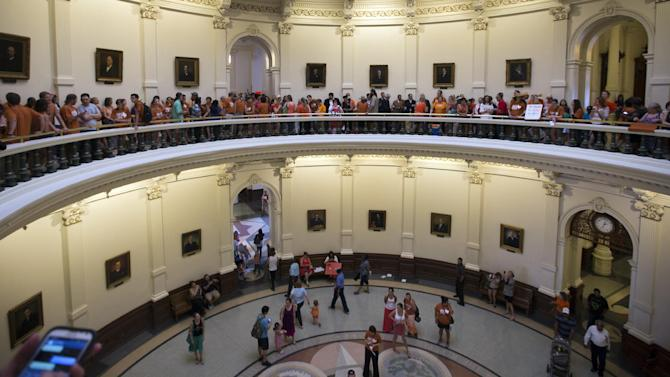 "A large crowd, many wearing Planned Parenthood T-shirts that read ""Stand with Texas Woman,"" wait in line to enter the house chambers at the Texas State Capitol in Austin, Texas on Sunday, June 23, 2013. More than 600 women's rights protesters crowded into the Texas Capitol to watch Democrats begin a series of parliamentary maneuvers to stop the Republican majority from passing some of the toughest abortion restrictions in the country. (AP Photo/Austin American-Statesman/Statesman.com, Ricardo B. Brazziell)"